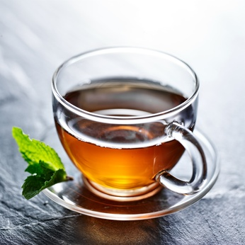 glass of hot tea with mint garnish